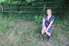 Девушка сидя на журнале Стоковые Изображения