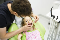 Девушка сидя на зубоврачебном стуле на ее регулярн зубоврачебном проверке Стоковое Изображение
