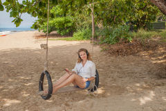 Девушка сидя на качании на тропическом пляже Стоковая Фотография