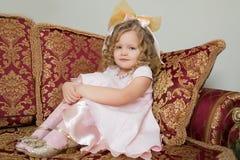 Девушка сидя на кресле обнимая его колени с его руками стоковое фото