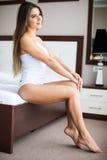 Девушка сидя на кровати дома просыпая вверх стоковое изображение