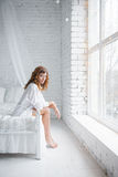 Девушка сидя на кровати Стоковые Изображения