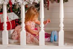 Девушка сидя на крылечке на рождественской елке Стоковые Фото