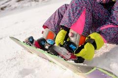 Девушка сидя на наклонах лыжи Стоковая Фотография RF