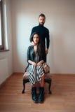 Девушка сидя на парне стула стоя за ей Стоковое фото RF