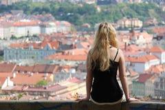 Девушка сидя на предпосылке перил городка - Праги Стоковые Фото