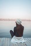 Девушка сидя на пристани и смотря реку Стоковые Изображения