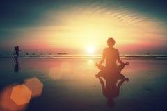 Девушка сидя на пляже во время захода солнца и размышляя в представлении йоги Стоковые Изображения