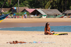 Девушка сидя на пляже наслаждаясь праздниками Стоковые Изображения