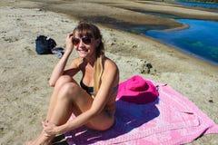 Девушка сидя на пляже Стоковые Фото