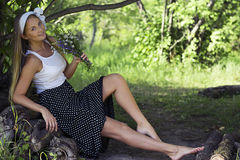 Девушка сидя на древесине и пахнуть пуком цветков Стоковое фото RF
