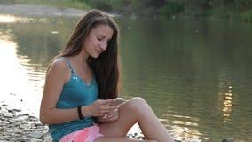 Девушка сидя на речном береге с печатать телефона сток-видео