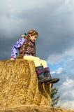 Девушка сидя на связках соломы Стоковые Фото