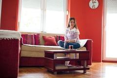 Девушка сидя на софе в живущей комнате Стоковое Изображение