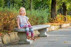 Девушка сидя на стенде в парке города Стоковая Фотография