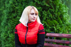 Девушка сидя на стенде в парке Стоковые Фото