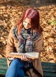 Девушка сидя на стенде в парке Стоковое Фото