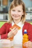 Девушка сидя на таблице в еде нездоровом Packe школьного кафетерия стоковая фотография rf