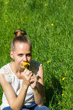 Девушка сидя на траве с одуванчиками в руках стоковая фотография rf