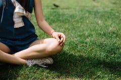 Девушка сидя на траве с пересеченными ногами в городской площади Стоковые Изображения
