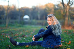 Девушка сидя на траве стоковое фото rf