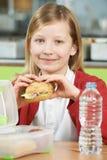 Девушка сидя на упакованной таблице в здоровой еды школьного кафетерия стоковое изображение rf