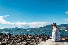 Девушка сидя на утесе на пляже Kitsilano в Ванкувере, Канаде Стоковое Изображение RF
