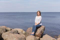 Девушка сидя на утесе Стоковые Изображения