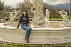 Девушка сидя на фонтане Стоковые Фотографии RF