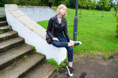 Девушка сидя около лестниц Стоковое Изображение RF