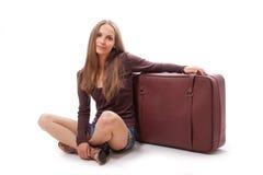 Девушка сидя около изолированного чемодана, на белизне Стоковые Изображения