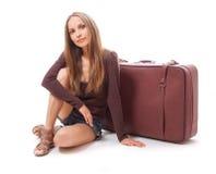 Девушка сидя около изолированного чемодана, на белизне Стоковая Фотография