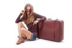 Девушка сидя около изолированного чемодана, на белизне Стоковое Изображение RF
