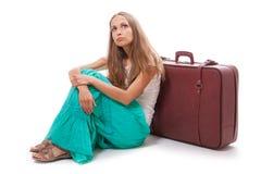Девушка сидя около изолированного чемодана, на белизне Стоковое Фото