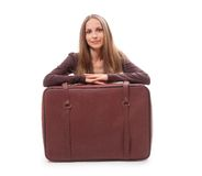 Девушка сидя около изолированного чемодана, на белизне Стоковая Фотография RF