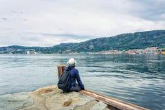 Девушка сидя около моря самостоятельно Стоковая Фотография RF