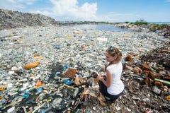 Девушка сидя около озера покрытого с пластичными бутылками Стоковые Изображения