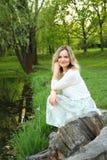 Девушка сидя около озера стоковая фотография rf