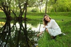 Девушка сидя около озера стоковое фото rf