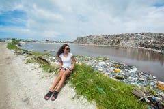 Девушка сидя около реки заполнила с пластичными бутылками на свалке мусора Стоковая Фотография