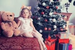 Девушка сидя около рождественской елки на софе с плюшевым медвежонком стоковое фото rf
