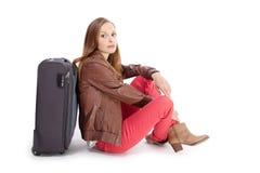 Девушка сидя около чемодана Стоковое Фото