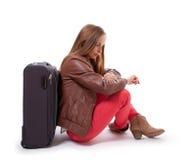Девушка сидя около чемодана Стоковое Изображение