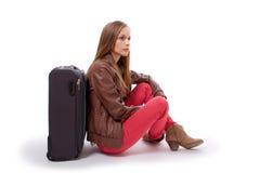 Девушка сидя около чемодана Стоковые Фотографии RF