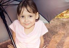 Девушка сидя под зонтиком Стоковые Фото