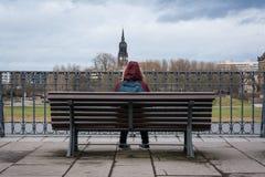 Девушка сидя самостоятельно на ландшафте Дрездене w города зимы стенда холодном Стоковые Изображения