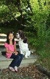 Девушка сидя с ее собакой Стоковые Изображения