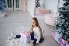 Девушка сидя с подарочными коробками приближает к рождественской елке дома Стоковое Изображение RF