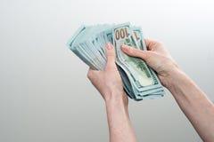Девушка сказала 10000 долларов в руке Стоковые Изображения