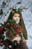 Девушка сказки Портрет маленькая девочка в платье оленей с покрашенной стороной в antler леса зимы большом коричневом стоковые изображения